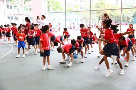 Primary one students competing against their classmates in the Indoor Basketball Court (IBC).